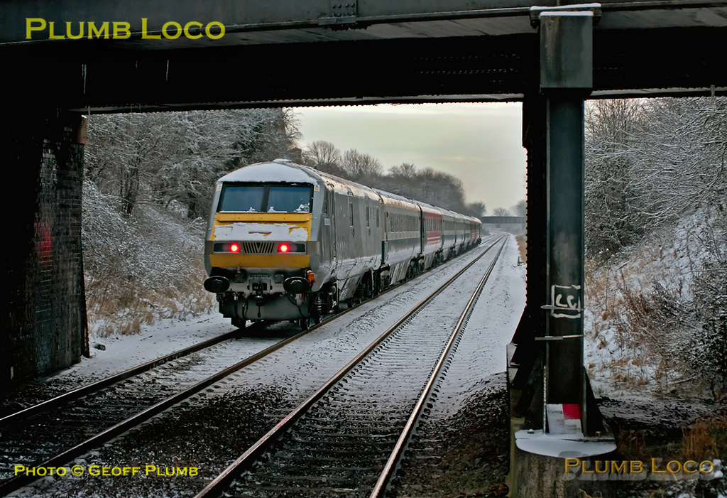 "DVT 82303 is on the rear of 1H08, the 06:53 Banbury to Marylebone train hauled by 67015 ""David J. Lloyd"" as it departs from the stop at Haddenham & Thame Parkway just a few minutes late at 07:22 on the snowy morning of Friday 10th February 2012. Digital Image No. GMPI10966."