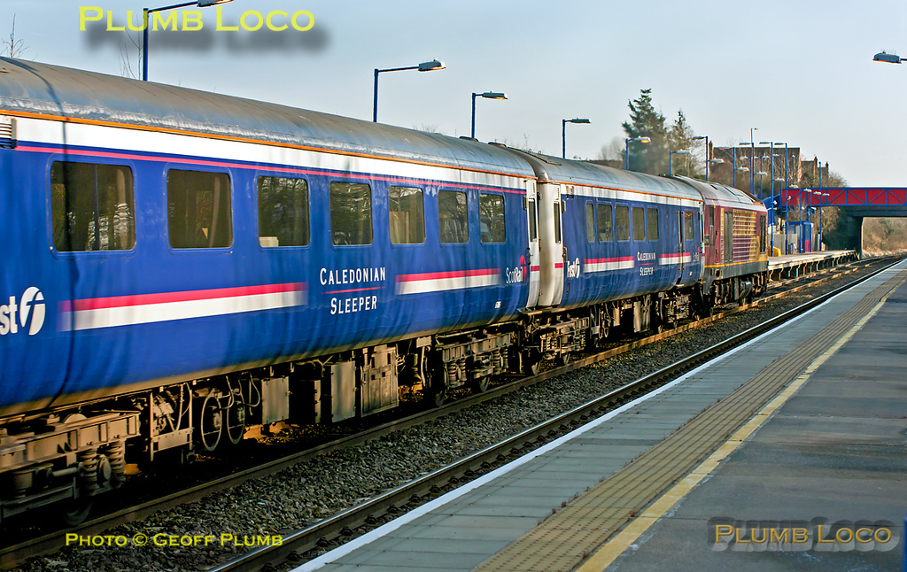 """Following the derailment at Bletchley in the early hours of the morning, 1M11 the """"Caledonian Sleeper"""", 23:40 from Glasgow Central to Euston, was terminated at Crewe. It then ran as 5M11, 11:40 ECS from Crewe to Euston and Wembley via the Chiltern line. Here the 16 coach train is passing through Haddenham station behind 67017, running a couple of minutes early at 13:44 on Friday 3rd February 2012. Digital Image No. GMPI10883."""
