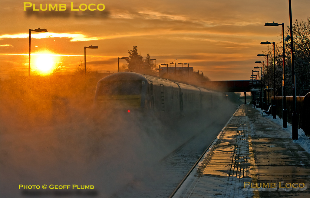 "The sun comes up in a blaze of glory over Haddenham & Thame Parkway station as 67018 ""Keith Heller"" speeds southwards in a cloud of thrown up snow at the head of 1F91 with DVT 82304 on the rear. This is the 06:55 from Birmingham Moor Street to Marylebone express passing through at 07:54 on Friday 10th February 2012. Digital Image No. GMPI10984."
