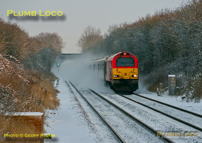 "As with the previous non-stop loco hauled train, much of this one is also obscured by the snow cloud thrown up by the 100mph passage of 67018 ""Keith Heller"" with 1F91, the 06:55 from Birmingham Moor Street to Marylebone express. It is approaching Haddenham station at 07:54, a few minutes late on the snowy morning of Friday 10th February 2012. Digital Image No. GMPI10982."