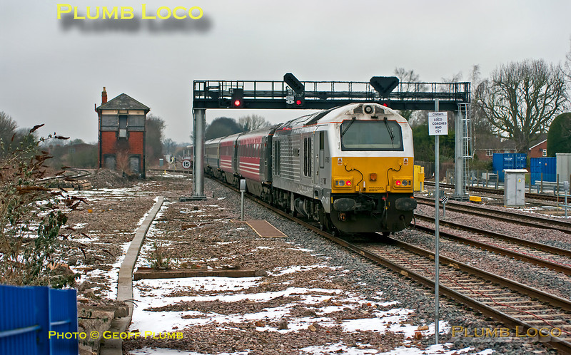 """Running slowly under a yellow signal (now changed to red) and a leaden winter sky, 82303 passes through Princes Risborough at the head of 5T67, 09:30 from Wembley LMD to Tyseley for tyre-turning on the seven coach Banbury set, AL02. 67015 """"David J. Lloyd"""" was providing the power on the rear. Note the new sign to indicate the stopping point for """"Chiltern - Loco Coaches and DVT"""", sadly, this sign, obviously necessary, rather ruins the approach shot from this vantage point... 10:10, Thursday 9th February 2012. Digital Image No. GMPI10941."""