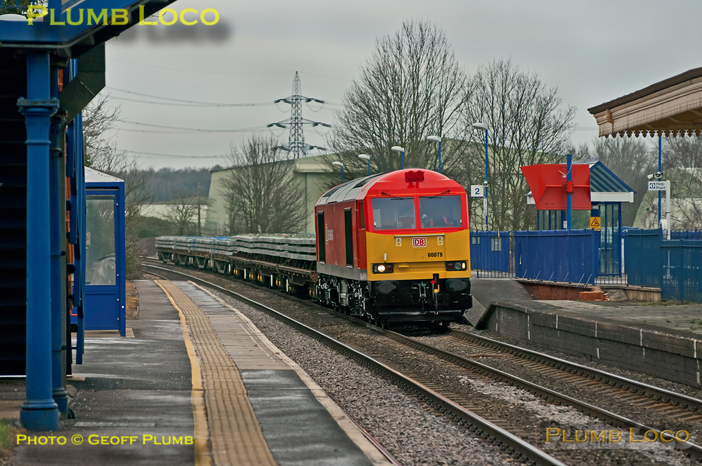 60079 has been recently outshopped in DB Schenker livery and looks a real treat. It had earlier worked 6V25 from Bescot to Hinksey and is now working the onward 6O26, 10:19 from Hinksey Yard to Eastleigh departmental train. Its wagons loaded with sleepers it is southbound through Culham station at  10:28 on the dull and very cold morning of Wednesday 8th February 2012. Digital Image No. GMPI10915.