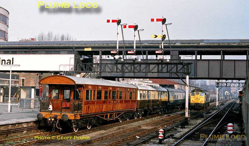 """In April 1974, Kensington Olympia station was still fully signalled with a wonderful mix of lower and upper quadrant semaphore signals. Here, three of the four tracks are occupied, on the right in the southbound platform loop is a special which I am aboard, while heading north on the through road is an unidentified Class 25 diesel. In the northbound platform loop is another private special headed by a """"Western"""" Class 52 diesel hydraulic which is graced on the rear by a wonderful ex-Great Western saloon coach and an even more wonderful ex-Great Eastern Railway balconied saloon coach No. 1. Slide No. 12558."""