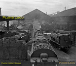 """Hasland MPD (18C),  near Chesterfield, on Sunday 12th August 1962 contains a wonderful selection of engines, from 0-4-0ST No. 47004, several 4F 0-6-0s including 44261 and possibly 44463, a couple of """"Jinties"""" (3F 0-6-0Ts), several 8F 2-8-0s, a Horwich """"Mogul"""" 2-6-0 (""""Crab"""") and in the foreground a Standard 9F 2-10-0. Virtually all are in steam, being prepared for the following day's work. The shed roof had been missing for years! B&W Neg No. 132."""