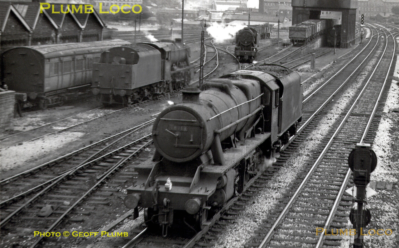 "LMS Stanier 8F 2-8-0 No. 48113 is working light engine tenderfirst passing Mirfield MPD, where a fellow 8F (unidentified) is on shed, WD 2-8-0 No. 90397 is pottering about in the yard and another unidentified engine is under the combined water and coaling stage. Some examples of the ""speed-signalling"" system here can be seen, the signal by the water tank showing all three aspects! Summer 1966."