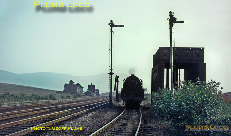 BR Standard 9F 2-10-0 No. 92123 has stopped for water alongside the water tank in the down loop at Blea Moor, with a train of empty wagons bound for Long Meg. Flat-topped Ingleborough can just be made out through the distant haze of a summer day. Monday 21st August 1967. Slide No. 3036.