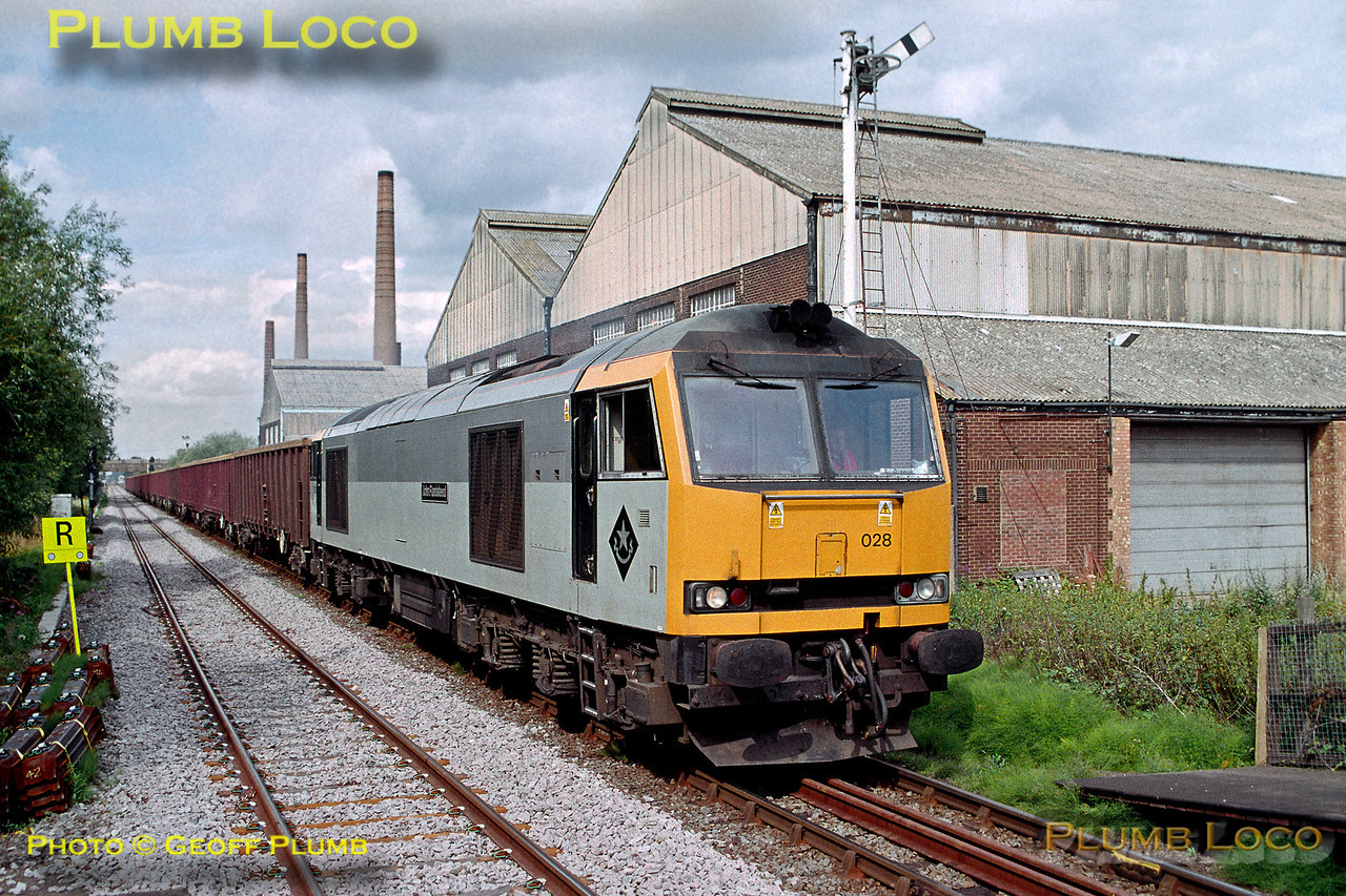 "EWS 60028 ""John Flamsteed"" passing Stewartby brickworks and approaching the station at 15:55 on Monday 19th July 2004. It has just left Forders Sidings on time with 6Z74, the 15:50 train of empty MBA spoil wagons returning to King's Cross. The train ran as required, and was diverted to Calvert during the Marston Vale line blockade from 24th July 2004. Slide No. 33126."