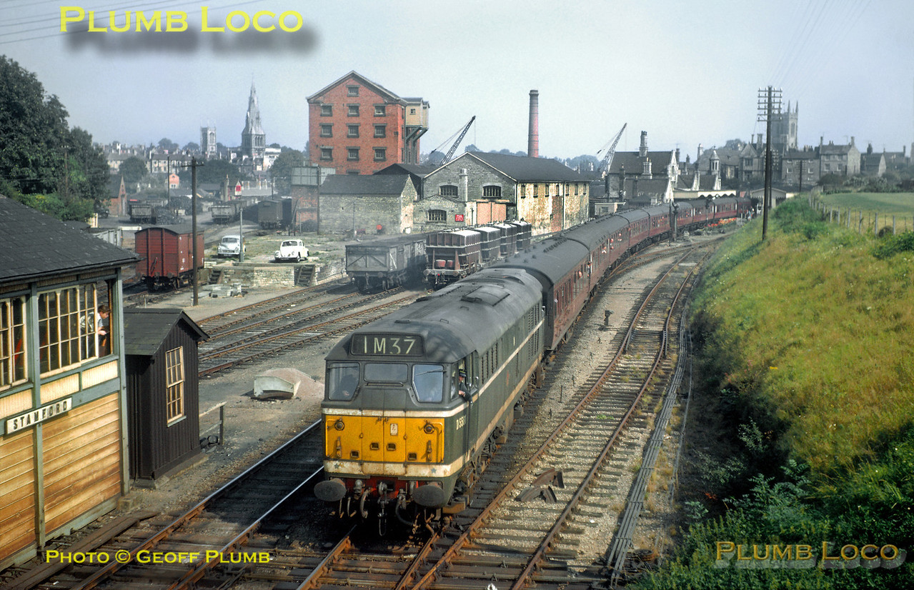 From the Geoff Plumb Collection of original slides. Brush Type 2 diesel No. D5581 (later class 31 No. 31163) still carries its original livery as it works a passenger train past the signalbox at Stamford with a Peterborough to Leicester train, though as it's carrying a headcode of 1M37 and has quite a lengthy set of coaches, it maybe something more exotic, especially as there are quite a few heads out of windows! Photo taken sometime in the summer of 1964, photographer unknown. From information received - 1M37 was the 09.30 Yarmouth Vauxhall to Derby Midland service, Saturdays Only, 27th June to 5th September 1964. Collect Slide No. 28682.