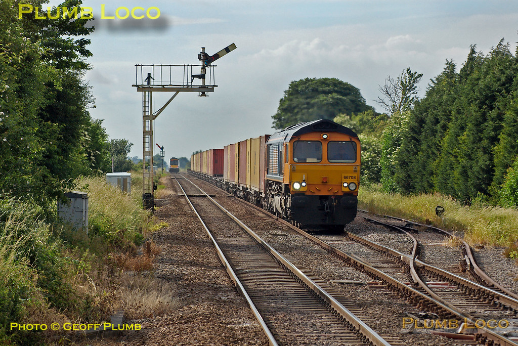 GBRf Class 66/7 No. 66708 approaches Manea station under semaphore signals with 4L78, the 11:41 Selby to Felixstowe container train at 17:26 on Tuesday 15th June 2004. 170 398 is disappearing in the distance with a westbound working. Digital Image No. IMGP0318.
