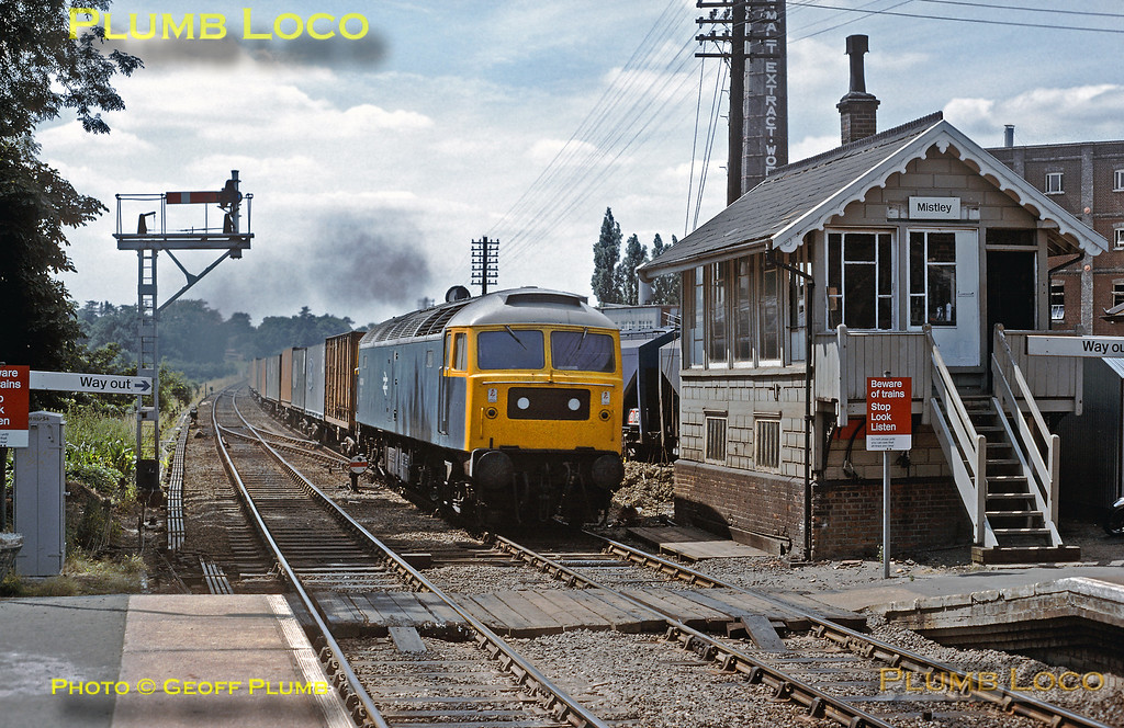 Class 47/0 No. 47004 in BR Blue livery with Stratford white roof, works a container train (mainly Ford cars) along the branch from Manningtree to Harwich approaching Mistley station on a lovely July day in 1979. Slide No. 14577.