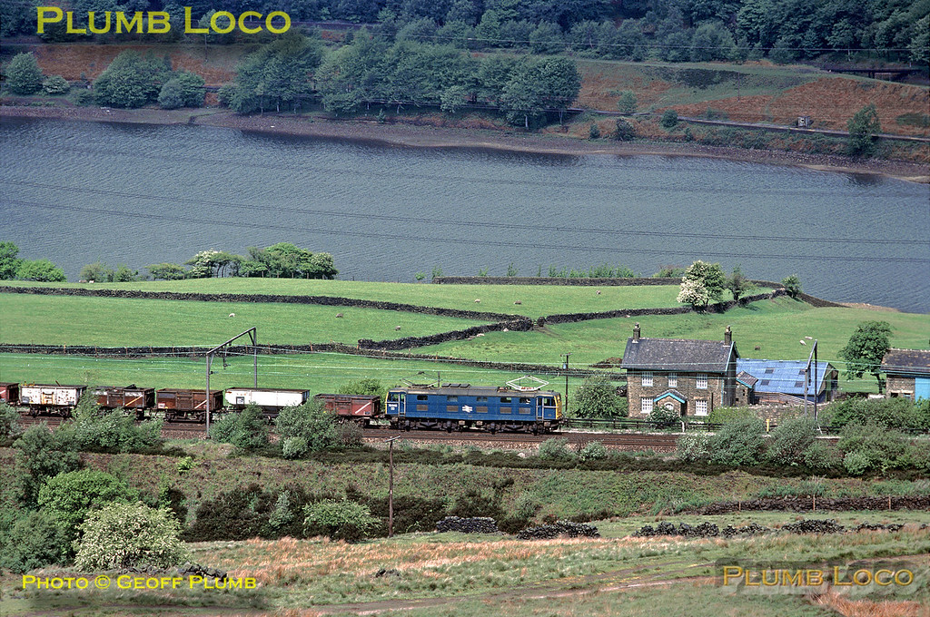 EM1 Class 76 Bo-Bo 1500v DC electric No. 76046 heads east towards Woodhead Tunnel alongside Torside Reservoir with a train of 16 ton mineral wagons and hoppers, some of which seem to be loaded with scrap. Saturday 11th June 1977. Slide No. 14083.