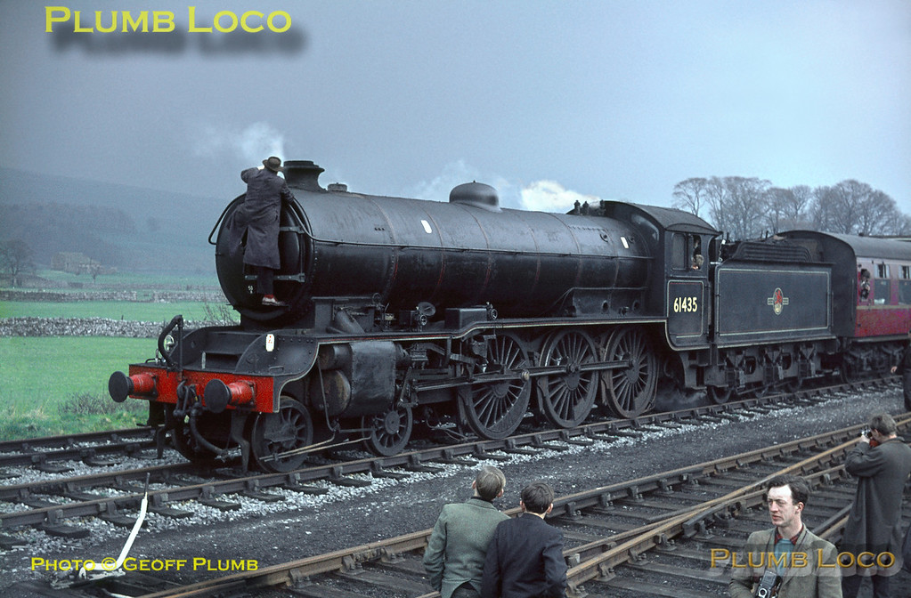 "In somewhat threatening looking weather conditions, B16/2 Class 4-6-0 No. 61435 has now reached the station precincts at Hawes and is about to be uncoupled from the train to run round. The loco inspector has climbed up onto the smokebox to remove the RCTS headboard and headcode lamps, prior to replacing them on the back of the tender for the run back towards Northallerton. This train, the RCTS ""North Yorkshireman"" Railtour, was the last passenger train to reach Hawes before the track was lifted. Hopefully, the Wensleydale Railway will once again run into Hawes, if their plans reach fruition. Saturday 25th April 1964. Slide No. 609."