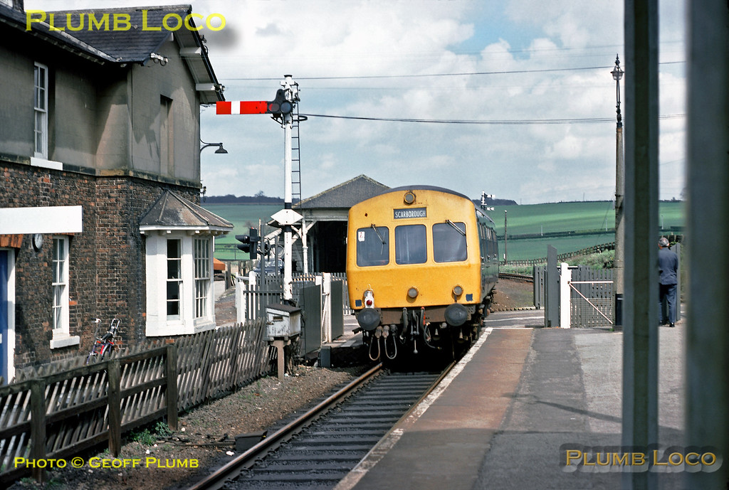 """A DMU in BR Blue livery sets off from Seamer station with a train from York to Scarborough across the level-crossing. The signal has already been returned to """"danger"""" so that the gates can be opened for road traffic as soon as the train has cleared the crossing. The goods yard and shed were still in use at this time. Thursday 28th April 1977. Slide No. 13991."""