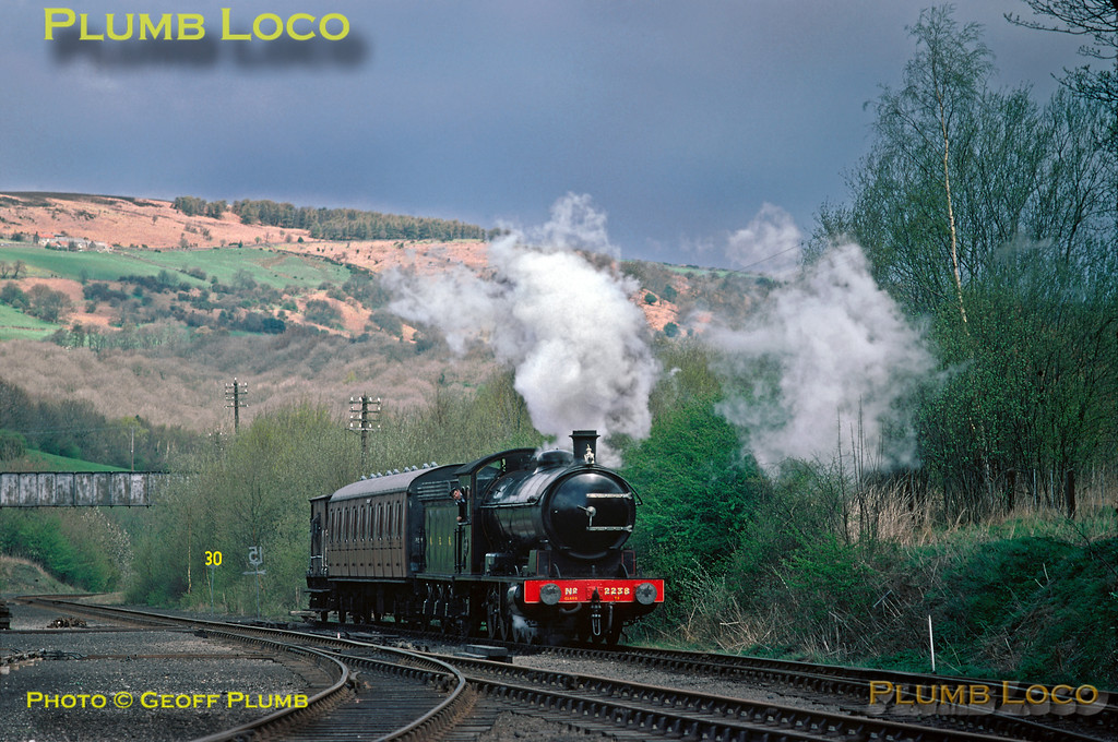 Under a rather treatening sky, NER T2 class 0-8-0 No. 2238 (LNER & BR class Q6 No. 63395) sits in the backshunt of the NYMR sidings at Grosmont with a single BR Mk.I non-corridor compartment coach and a brakevan, prior to working to Goathland. The BR line from Middlesbrough curves in from the left, by this time reduced to single track and heads to Whitby under the bridge (since demolished). This alignment has been changed considerably to accommodate extended platforms and sidings for the NYMR. Sunday 24th April 1977. Slide No. 13954.