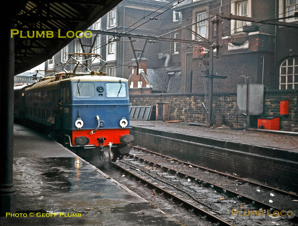 "EM2 Class Co-Co 1500v DC electric No. 27001 ""Ariadne"" waits at a very wet Sheffield Victoria station with the 10:45 departure for Manchester on Monday 17th February 1964. It is newly repainted in ""Electric Blue"" livery but has no yellow warning panel. The engine was later sold to the Netherlands Railways and eventually preserved. The Victoria Hotel still backs onto the site of the station which is now a weed grown wilderness with just one single track through to Deepcar. Slide No. 517."