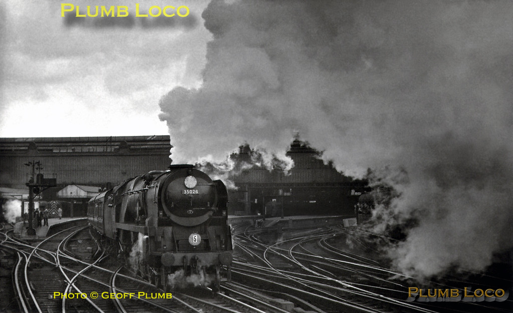 """Bulleid """"Merchant Navy"""" Class 4-6-2 No. 35026 """"Lamport & Holt Line"""" covers Waterloo station with a smokescreen as it departs with a west of England express, seen from a parallel departing train, Sunday 16th December 1962. B&W Neg No. 238."""