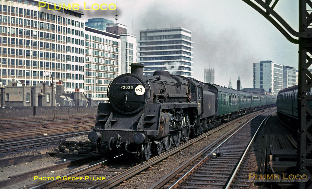 """BR Standard 5MT 4-6-0 No. 73022 approaches Vauxhall station alongside an EMU whilst in charge of the 09:50 excursion train from Waterloo to Bournemouth, carrying the headcode """"SPL 3"""", on the morning of Sunday 3rd July 1966. Slide No. 2147."""