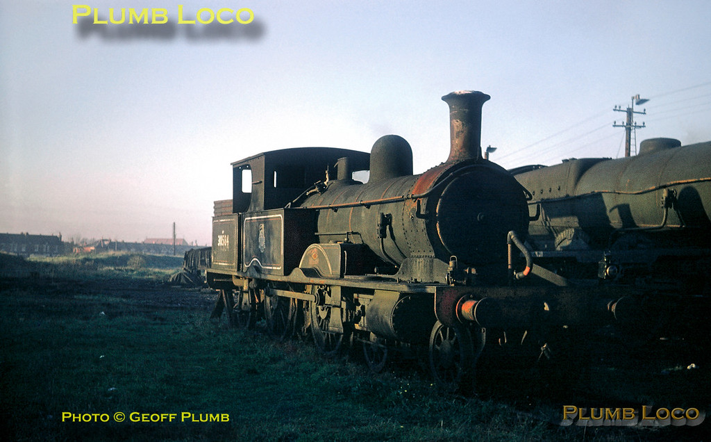 """From the Geoff Plumb Collection of original slides. LSWR Adams """"Radial Tank"""" 4-4-2T class 0415 No. 30584 sits dumped at Eastleigh depot after withdrawal from service. Three locos of the class survived to work the Lyme Regis branch but finally succumbed to progress. This loco and 30582 were scrapped, but 30583 was preserved on the Bluebell Railway. Alongside is """"Lord Nelson"""" class 4-6-0 No. 30855 """"Robert Blake"""", also awaiting its fate. 30584 was built by Dübs in 1885, works number 2109, and was withdrawn from Exmouth Junction shed in February 1961. It was scrapped at Eastleigh Works in December 1961. 30855 was built at Eastleigh Works in 1928 and was withdrawn from Eastleigh shed in September 1961, also being scrapped at Eastleigh in February 1962. Date uncertain, but most probably a winter afternoon in 1961, and photographer unknown. Collect Slide No. 29416."""