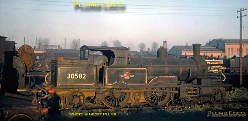 "From the Geoff Plumb Collection of original slides. LSWR Adams ""Radial Tank"" 4-4-2T class 0415 No. 30582 sits dumped at Eastleigh depot after withdrawal from service. Three locos of the class survived to work the Lyme Regis branch but finally succumbed to progress. This loco and 30584 were scrapped, but 30583 was preserved on the Bluebell Railway. Behind is ""Lord Nelson"" class 4-6-0 No. 30855 ""Robert Blake"", also awaiting its fate, and various locos can be seen in the yard beyond. 30582 was built by Robert Stephenson & Co. in 1885, works number 2608, and was withdrawn from Exmouth Junction shed in July 1961. It was scrapped at Eastleigh Works in March 1962.  Date uncertain, but most probably a winter afternoon in 1961, and photographer unknown. Collect Slide No. 29417."
