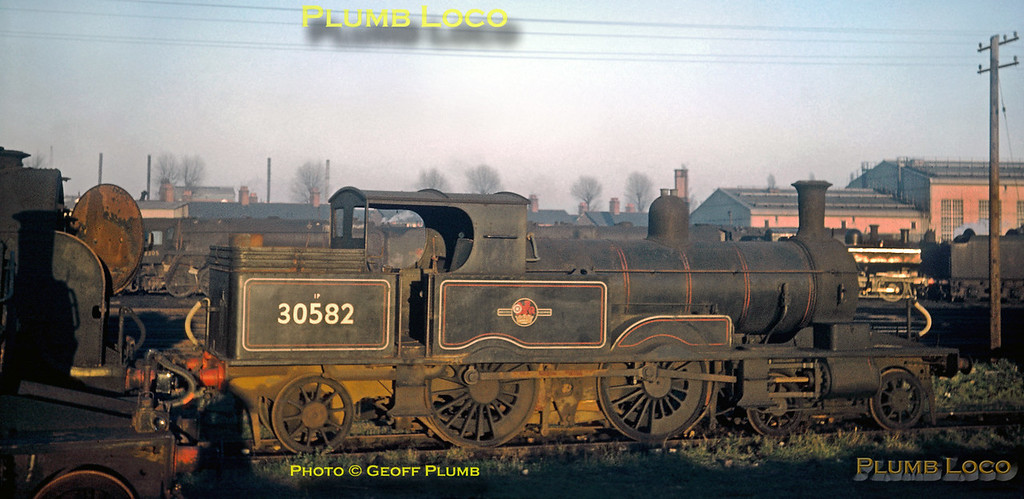 """From the Geoff Plumb Collection of original slides. LSWR Adams """"Radial Tank"""" 4-4-2T class 0415 No. 30582 sits dumped at Eastleigh depot after withdrawal from service. Three locos of the class survived to work the Lyme Regis branch but finally succumbed to progress. This loco and 30584 were scrapped, but 30583 was preserved on the Bluebell Railway. Behind is """"Lord Nelson"""" class 4-6-0 No. 30855 """"Robert Blake"""", also awaiting its fate, and various locos can be seen in the yard beyond. 30582 was built by Robert Stephenson & Co. in 1885, works number 2608, and was withdrawn from Exmouth Junction shed in July 1961. It was scrapped at Eastleigh Works in March 1962.  Date uncertain, but most probably a winter afternoon in 1961, and photographer unknown. Collect Slide No. 29417."""