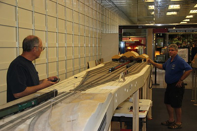 Larry operating a passenger train in the Oakland Mole module owned by him while Dave Grounds looks on.