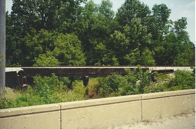 Johnson Drain at 5 Mile road near  Plymouth, MI. The bridge is a fairly typical pile truss bridge with a ballasted deck.  The trees must have been cleared out recently as looking at the location today 20 years later the trees are much larger and thickly grown in.