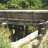 Johnson Drain at 5 Mile road near Salem, MI.  The bridge is a fairly typical pile truss bridge with a ballasted deck.