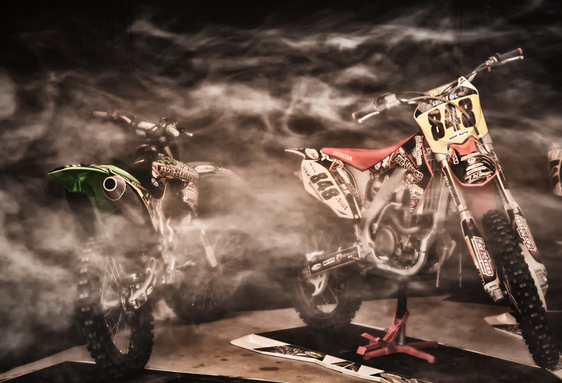 "Smoke filled shop with the racing bikes from the Denver Colorado motocross team, ""5 Stones Racing""."