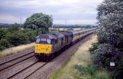 A pair of Class 31's pass Hutton Moor on the Weston-super-Mare avoiding line with a southbound Saturday holiday extra. 1980's.