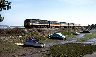 A very grubby 47851 heads the 14.15 Plymouth to Liverpool over Cockwood Harbour. 25th August 1991.