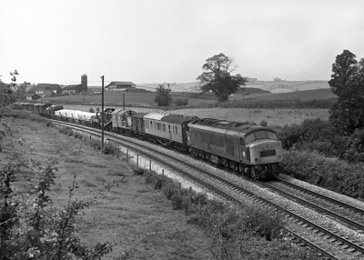 A Class 45 drops downhill to Totnes with a very mixed freight including Clay Hoods and engineers equipment. Summer 1977.