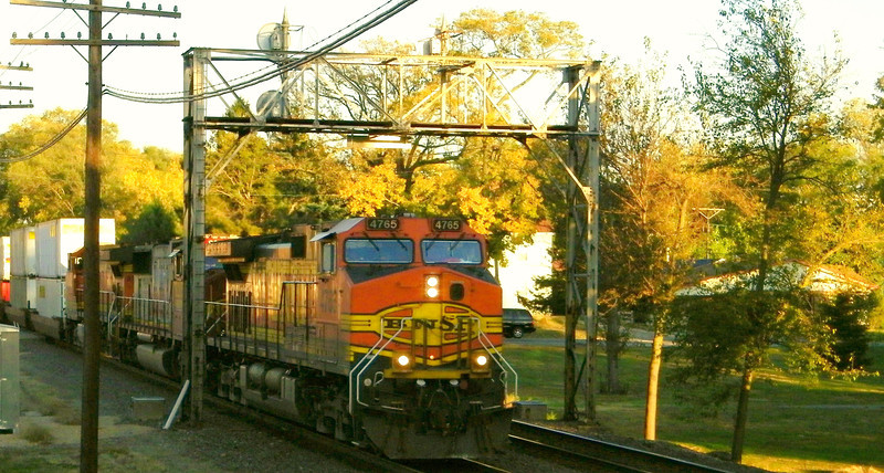 BNSF intermodal, with an old Santa Fe warbonnet paint job sandwiched in, nears the diamond.