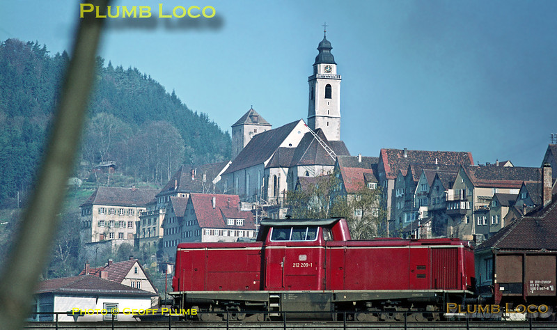 211 class diesel No. 212 209-1 comes down the grade from Eutingen into Horb on the main line from Stuttgart, passing over the Neckar bridge only a couple of minutes after P8 038 382-8 had gone the other way, with a freight train bound for Rottweil. Tuesday 5th May 1970. Slide No. 4879.