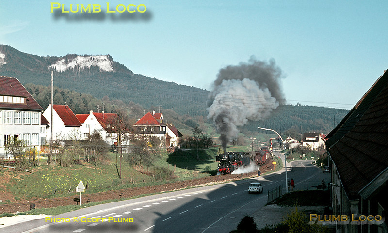 It was not a hardship to be up early to see (and hear!) things like this from the bedroom window of the Fremdenzimmer in which I was staying in the village of Laufen. The morning sun is still low in the sky as Class 50 2-10-0 No. 050 383-9 slogs up the 1 in 48 gradient from Laufen station with a freight train for Sigmaringen from Tübingen on another gorgeous morning, Friday 8th May 1970. Despite the spectacle, various locals go about their business oblivious to the audio visual display! Slide No. 5023.