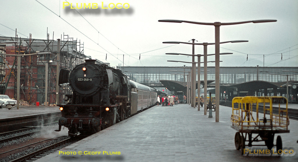 023 059-9 has just arrived into Heidelberg with a train from Tübingen and the passengers alight onto the rain-soaked station, now beginning to dry off. Tuesday 12th May 1970. Slide No. 5117.
