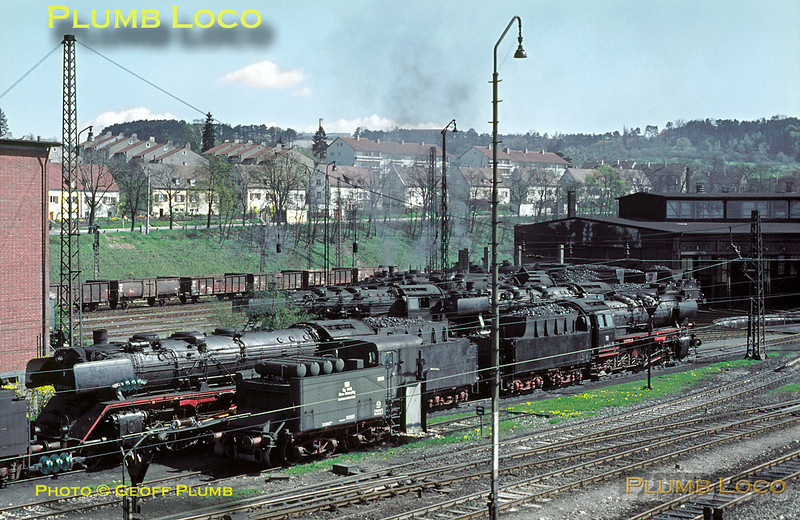 """General view of the Bahnbetriebswerk (engine shed!) at Ulm with a goodly collection of locos """"on shed"""". These are mostly Class 50 2-10-0s with at least one 03 Pacific, No. 003 248-2. Most of the locos look quite clean. Nearest vehicle to the camera is a converted old loco tender, now a snowplough. Saturday 9th May 1970. Slide No. 5079."""