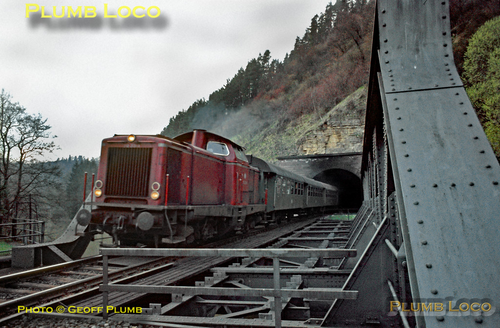 A V100 diesel, possibly 212 223-3, emerges from a tunnel and immediately crosses a bridge over the River Neckar as it approaches Rottweil with another southbound local passenger train. Monday 4th May 1970. Slide No. 4858.