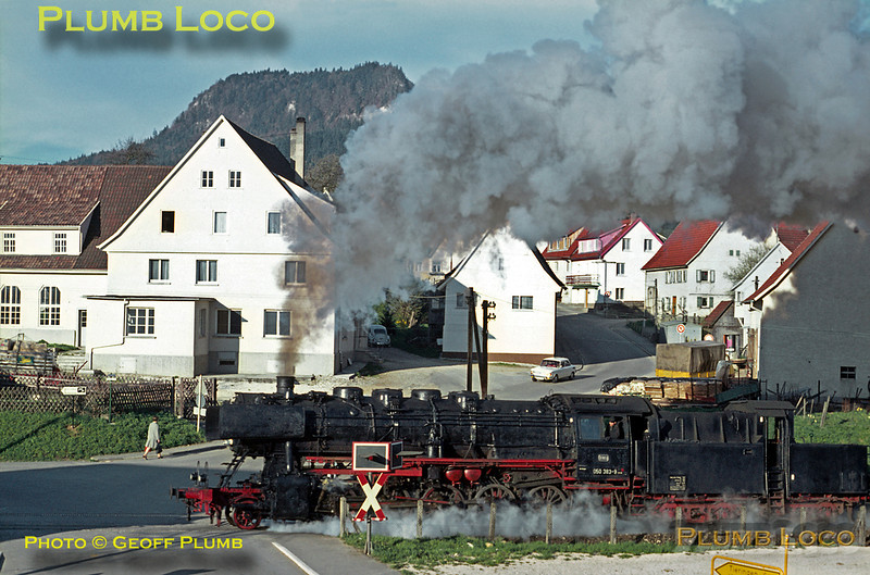 It was not a hardship to be up early to see (and hear!) things like this from the bedroom window of the Fremdenzimmer in which I was staying in the village of Laufen. The morning sun is still low in the sky as Class 50 2-10-0 No. 050 383-9 slogs up the 1 in 48 gradient from Laufen station with a freight train for Sigmaringen from Tübingen on another gorgeous morning, Friday 8th May 1970. Despite the spectacle, various locals go about their business oblivious to the audio visual display! Slide No. 5026.