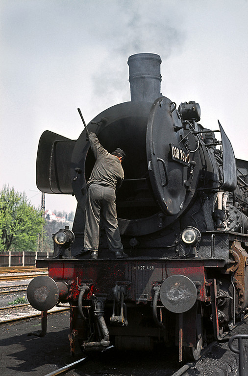 038 791-0 has just come on shed and one of the staff clears out the ash from the smokebox as it stands over the ashpits at Tübingen loco depot. Wednesday 6th May 1970. Slide No. 4979.