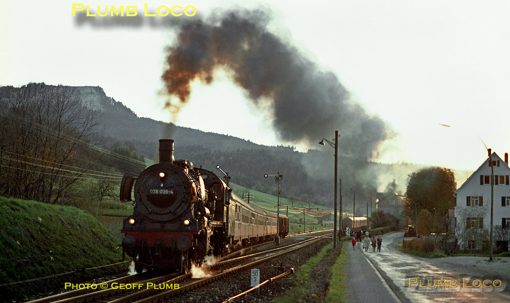 038 711-8 and its train have stopped in the station at Laufen in the background and now 038 039-4, which has been waiting for it to clear the single track, can now start away in fine style up the 1 in 48 gradient towards Lautlingen and Ebingen with its train from Tübingen to Sigmaringen as the sun sets over the Schwäbischen Alb on the evening of Thursday 7th May 1970. Slide No. 5021.