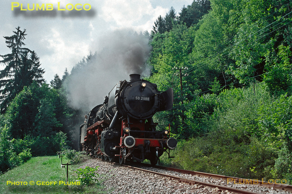 Ex-DB 2-10-0 No. 50 2988 is working the 15:55 train from Weizen to Zollhaus-Blumberg along the preserved Wutachtalbahn (Sauschwänzlebahn) and has just emerged from Grimmelshofener Tunnel on the long climb around many curves, including a spiral tunnel. Wednesday 14th August 1991. Slide No. 22151.