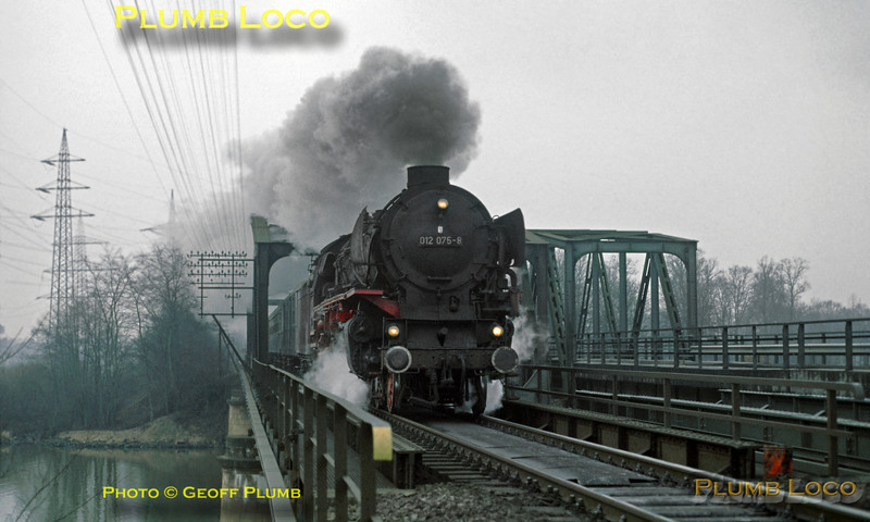 """This was my last sight of """"normal service"""" German steam in action, as opposed to in preservation or narrow gauge, and quite a nice way to go out... 01/10 class 4-6-2 No. 012 075-8 is in full cry at the head of a northbound express passenger train from Rheine to Emden, just north of Elbergen. It is crossing the combined rail/road girder bridge over the combined rivers Ems and Grosse Aa together with the Dortmund - Ems Kanal on what at the time had become a single track section over the bridge - nowadays restored to double track. Thursday 6th March 1975. Slide No. 13180."""