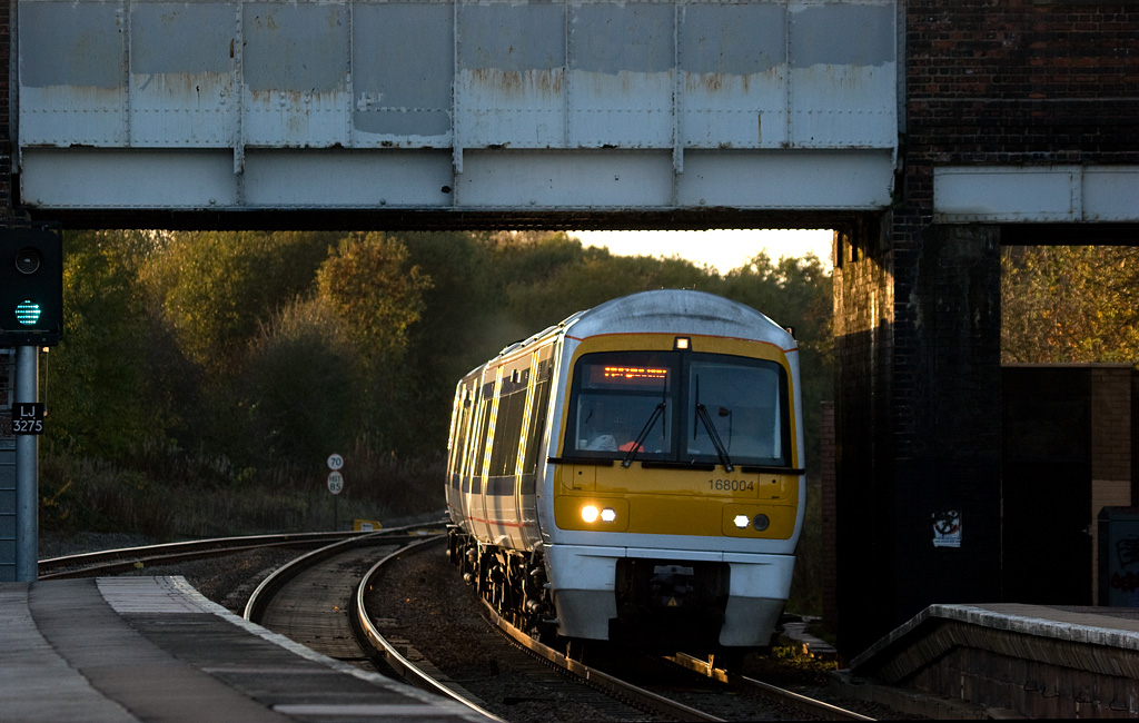 The last rays of the setting sun glint off a 168/0 as it hustles underneath the road bridge and through Hatton station.  Chiltern Railways 168 004 in Hatton.