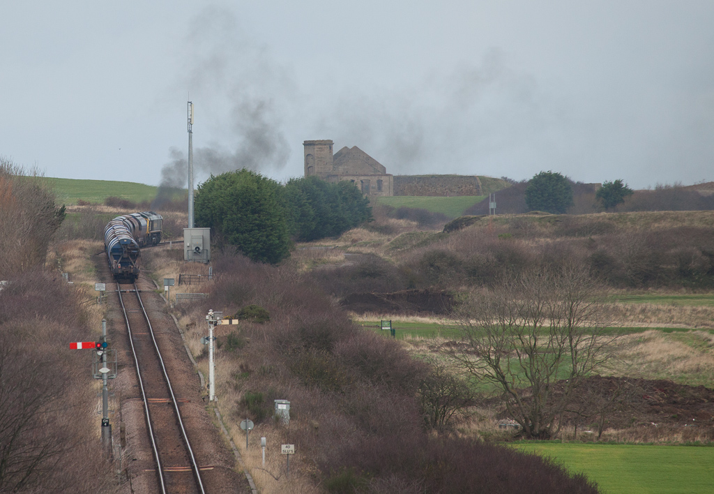 Freightliner Heavy Haul 66599 on a potash load from Boulby passes the Huntcliffe Mine fan house.