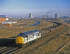 On 19th December 1990, 37507 HARTLEPOOL PIPE MILL  brightens the scene at Cargo Fleet, just 2 days before the shortest day, as it trundles towards Tees Yard with a short train of profiled steel from Skinningrove.
