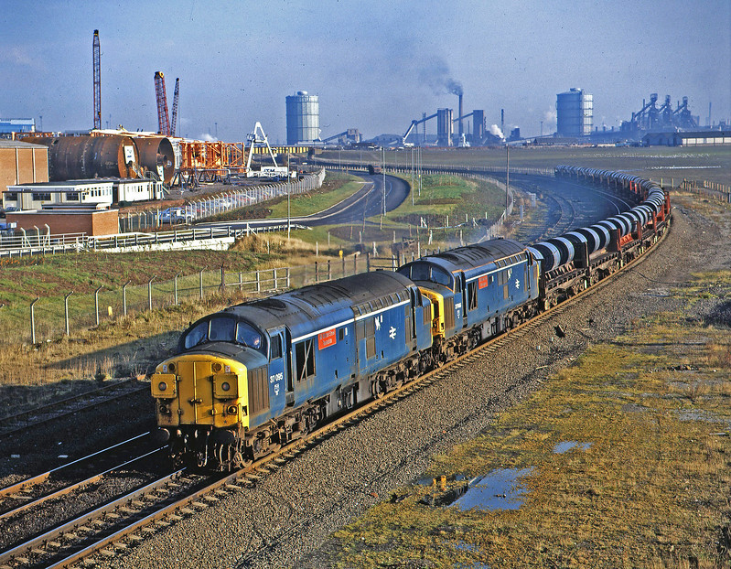 Metals dedicated pair 37095+37066 are setting off on their long journey to Corby with 1500 tons of hot rolled coil from BSC Lackenby.. Seen here passing Cargo Fleet at about 11.00 on 19th November 1986. This daily train ran EWD but also occasionally SSuO. It helped me to enjoy my morning coffee break – even though I worked in Newcastle.