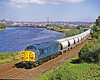 Against a backdrop of the not so coally Tyne, 37023, clean but workworn, has a lengthy train of lime and limestone empties forming 6M46, Redcar to Hardendale. This picture demonstrates just how invaluable Class 37s were when railfreight was more buoyant. This flow was dealt with on a slip working basis, which means that this long train will return loaded tomorrow. No doubt 2 x 37s will work tomorrow's 6M46 to provide sufficient power to get the return heavy train up the long climb from Carlisle to Low Row. 25th June 1990