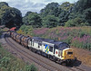 Bearing construction sector decals and proudly displaying its Buxton depot gritstone logo 37686 is unusual power(vice 47) for the Dalry to Tees chemical train as it slows for the sharp curve through Stocksfield station on 25th July 1994. This location is completely treed out now.