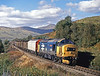 On a superb early autumn afternoon 37412 LOCH LOMOND rattles down past Inverhaggernie with a varied consist on the mid-day Fort William to Mossend freight. 29th September 1987.