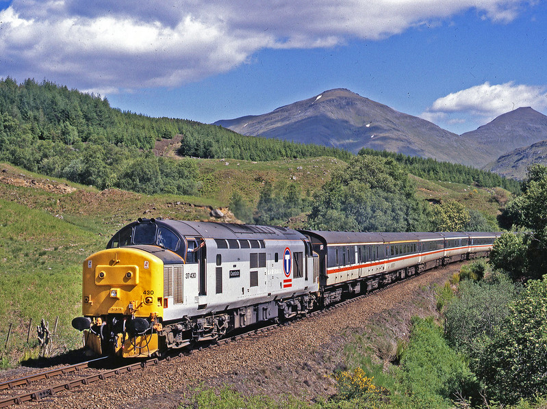 A cheery wave from the driver as 37430 throbs noisily up the gradient from Crianlarich to Upper Tyndrum past Inverhaggernie working the sleepers crossover train on a magical West Highland day – 14th June 1995.